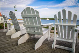 a set of Adirondack chairs on a deck