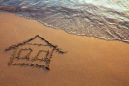 a house drawn in sand on a beach