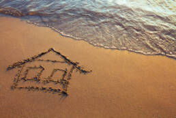a house drawn in sand on a beach