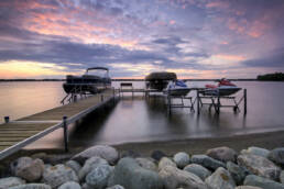 two boats and two jet skis on a dock at sunset time